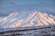 An early season snow dusts the Alaskan Range of mountains at sunset in Denali National Park, McKinley Park, Alaska