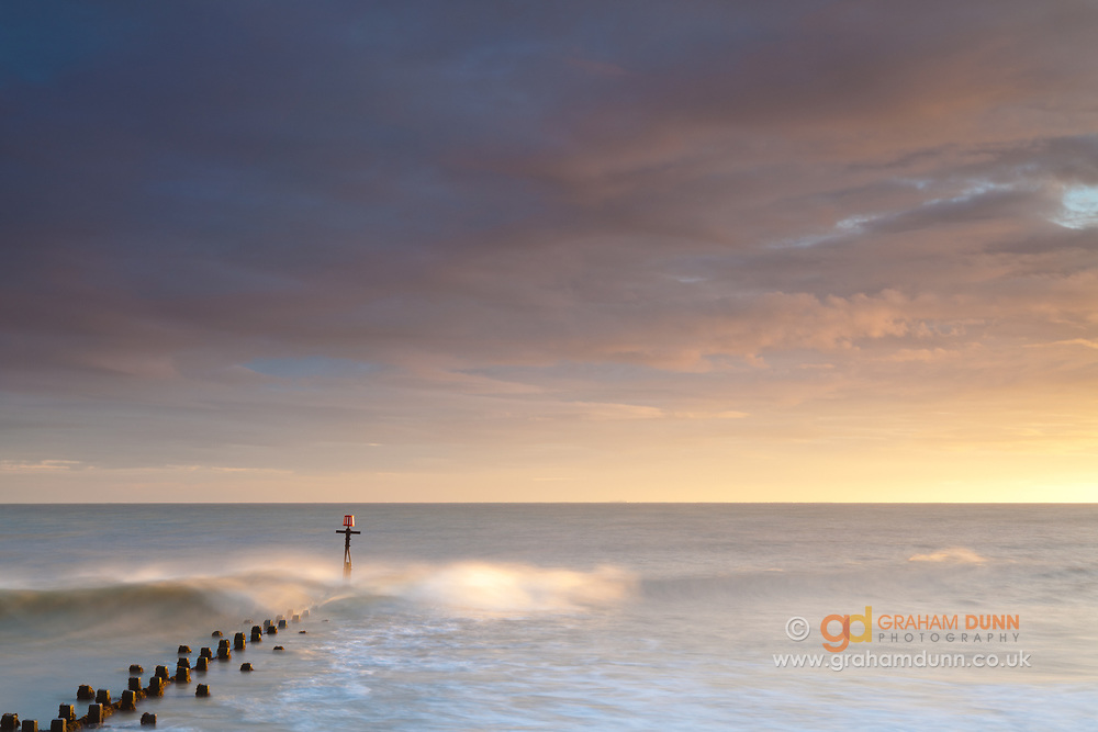 Dawn sunlight highlights a wave as it breaks over a groyne at West Runton. North Norfolk, East Anglia.