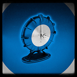 Vintage Atomic Era Modernist Europa Sunburst Executive Clock Photo illustration in blue
