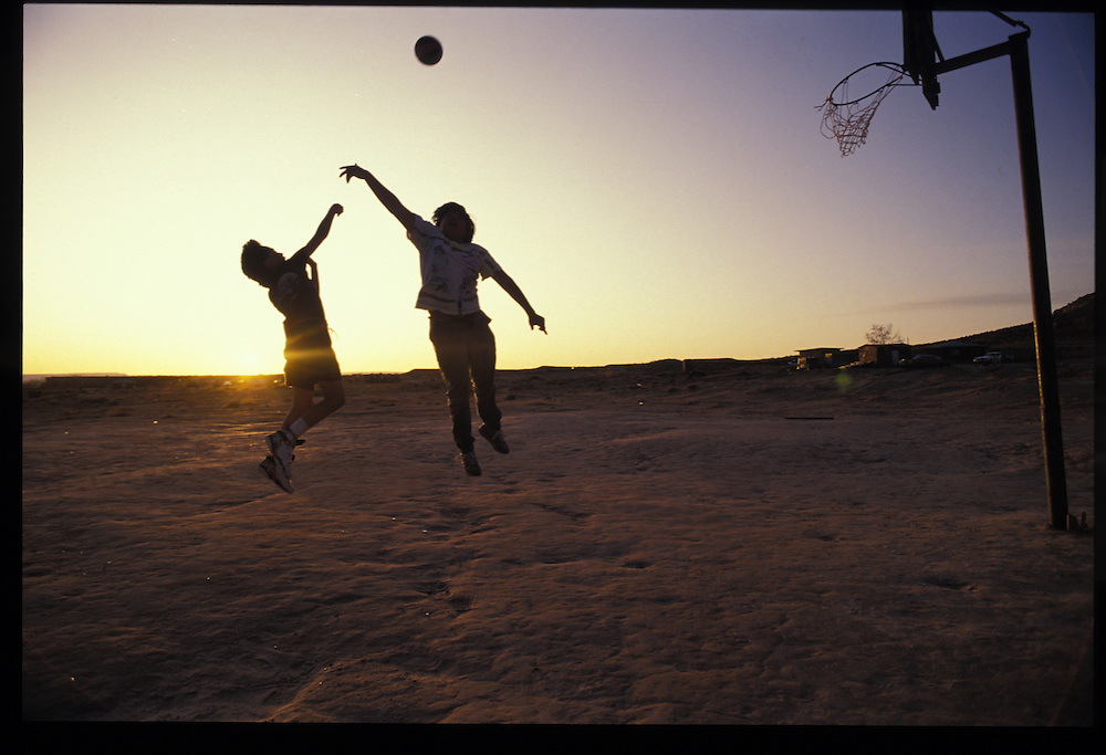 Junior Billy(10) and Fabian Denesto(15) play basketball at the site of the old airport in Tuba City.  Thousands of kids in isolated sheep camps learn to shoot through homemade bailing-wire hoops.