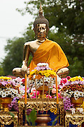 "15 JULY 2011 - PHRA PHUTTHABAT, SARABURI, THAILAND:  A robed statue of the Buddha is showered with flowers during the Tak Bat Dok Mai at Wat Phra Phutthabat in Saraburi province of Thailand, Friday, July 15. Wat Phra Phutthabat in Phra Phutthabat, Saraburi, Thailand, is famous for the way it marks the beginning of Vassa, the three-month annual retreat observed by Theravada monks and nuns. The temple is highly revered in Thailand because it houses a footstep of the Buddha. On the first day of Vassa (or Buddhist Lent) people come to the temple to ""make merit"" and present the monks there with dancing lady ginger flowers, which only bloom in the weeks leading up Vassa. They also present monks with candles and wash their feet. During Vassa, monks and nuns remain inside monasteries and temple grounds, devoting their time to intensive meditation and study. Laypeople support the monastic sangha by bringing food, candles and other offerings to temples. Laypeople also often observe Vassa by giving up something, such as smoking or eating meat. For this reason, westerners sometimes call Vassa the ""Buddhist Lent."" The tradition of Vassa began during the life of the Buddha. Most of the time, the first Buddhist monks who followed the Buddha did not stay in one place, but walked from village to village to teach. They begged for their food and often slept outdoors, sheltered only by trees. But during India's summer rainy season living as homeless ascetics became difficult. So, groups of monks would find a place to stay together until the rain stopped, forming a temporary community. Wealthy laypeople sometimes sheltered monks on their estates. Eventually a few of these patrons built permanent houses for monks, which amounted to an early form of monastery.   PHOTO BY JACK KURTZ"