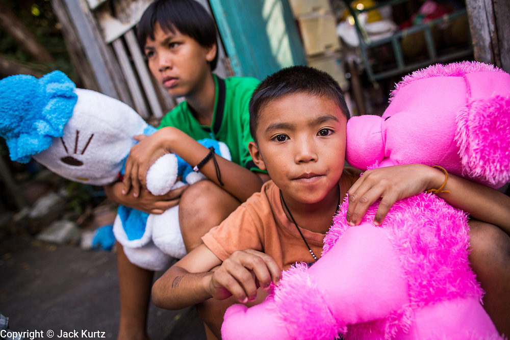13 JANUARY 2013 - BANGKOK, THAILAND:  Children with their toys in the Bang Luang neighborhood of Bangkok. The Bang Luang neighborhood lines Khlong (Canal) Bang Luang in the Thonburi section of Bangkok on the west side of Chao Phraya River. It was established in the late 18th Century by King Taksin the Great after the Burmese sacked the Siamese capital of Ayutthaya. The neighborhood, like most of Thonburi, is relatively undeveloped and still criss crossed by the canals which once made Bangkok famous. It's now a popular day trip from central Bangkok and offers a glimpse into what the city used to be like.   PHOTO BY JACK KURTZ