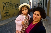 A mother holds her young daughter in a cobbled street of Lisbon's Biarro Alto district. With graffiti on the wall behind them and the city street stretching off in the distance, the couple of Portuguese family members stand on the cobbles. The mother smiles but the little girl looks distrustful and slightly nervous. Bairro Alto is one of the oldest districts in Lisbon. Dozens of fado singing clubs animate the area. All major Portuguese newspapers once had their offices in here. Prostitution was visible and considerable. Since the 1990s, Bairro Alto went through major changes. Lisbon's city council made extensive repairs, and dozens of new restaurants, clubs and trendy shops were opened. Many young people moved into the area. Cars were banned (except for residents and emergency vehicles).