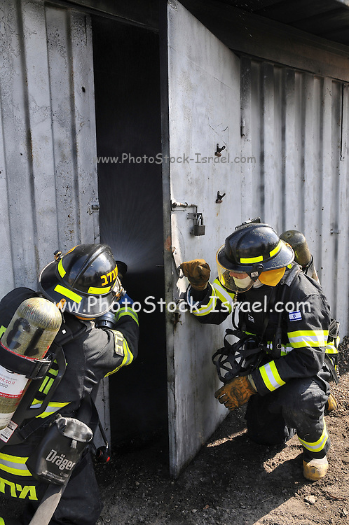 Firefighters with protective equipment prepare to enter a smoke filled room