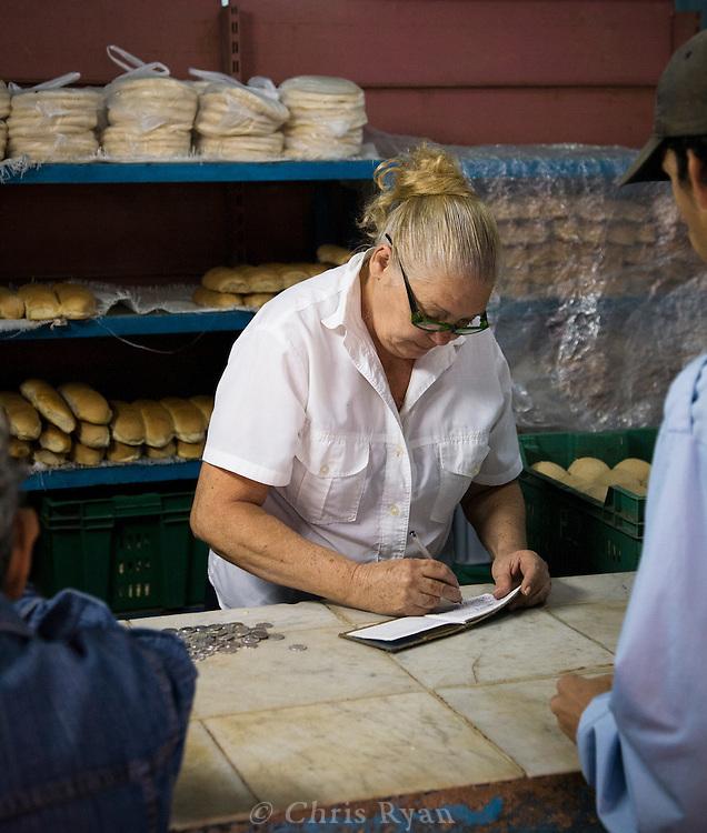 Clerk marking ration book at bread store, Havana, Cuba