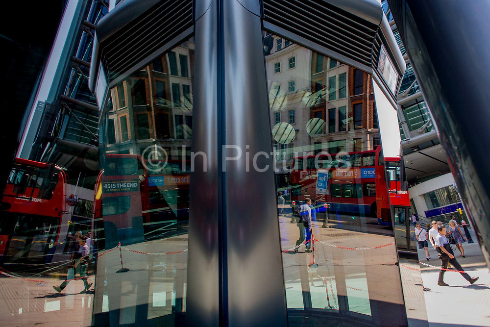 Londoners seen reflected in multiple plate glass windows on a busy summer lunchtime, in the Square Mile, the capital's historic financial district. As pedestrians walk to and from their surrounding offices, a red London bus continues its journey on its inner-city route past the vertical columns of steel. A red and white plastic chain barrier prevents them from entering the zone where, above - workers are cleaning an upper floor. The large windows are located on the corner of Cannon Street and Walbrook, both ancient thoroughfares in this ancient city, dating back to before Roman occupation.