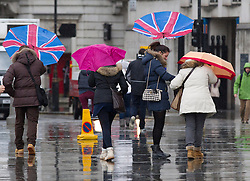 © Licensed to London News Pictures. 23/12/2013. London, UK. A tourist tries to control her umbrella outside Westminster Abbey in London today (23/12/2013). Weather warnings were yesterday issued for the United Kingdom predicting severe wind and rain that may affect holiday travel. Photo credit: Matt Cetti-Roberts/LNP