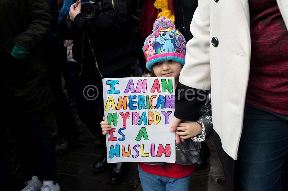 Stop Trump's Muslim ban demonstration on 4th February 2017 in front of the US Embassy in Grosvenor Square, London, United Kingdom. The protest was called on by Stop the War Coalition, Stand Up to Racism, Muslim Association of Britain, Muslim Engagement and Development, the Muslim Council of Britain, CND and Friends of Al-Aqsa. Thousands of demonstrators gathered to demonstrate against Trumps ban on Muslims, saying it must be opposed by all who are against racism and support basic human rights, and for Theresa May not to collude with him. A child holds a placard which says I am an American. My daddy is a Muslim.