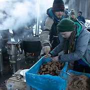 The second day of the Strike WEF march on Davos, 20th of January 2020, Switzerland. Lunch break. Food for 500 people, including sweet donuts and hot drinks is cooked out door by a cooking collective, all vegan and tasty. The march started in Schiers and walked the 24 kilomers to Klosters.  The aim is to finish in Davos with a public meeting in the town on the day the WEF begins. The march is a three day protest against the World Economic Forum meeting in Davos. The activists want climate justice and think that The WEF is for the world's richest and political elite only.