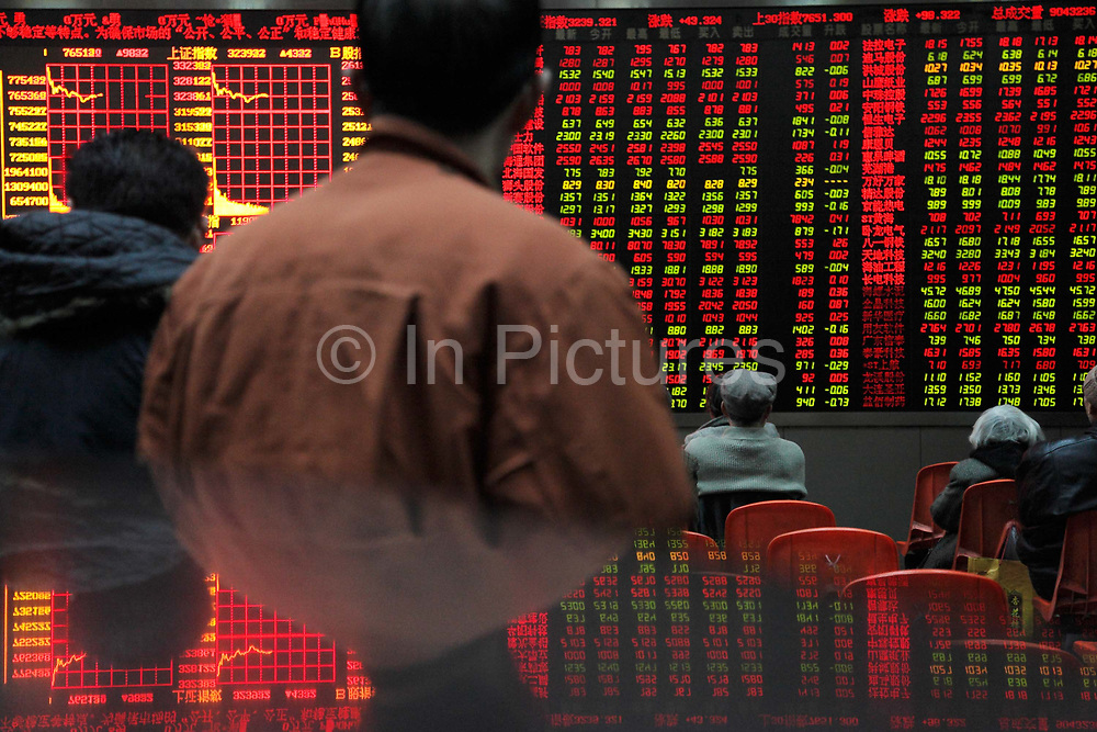 Investors watch the stock trading board at a securities exchange house in Shanghai, China on 11 January 2010.    Despite the country's robust economy, China's stock market has not been kind to the ordinary investors, it is one of the worst performing major markets in recent years.