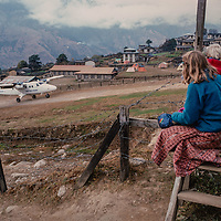 Meredith Wiltsie & 3-year old son Ben watch a  Twin-Otter STOL bush plane landing at Lukla airstrip, the gateway to  Mount Everst and the Khumbu region, Nepal.