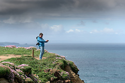 A tourist taking a photograph as he stands on the cliffs at Carnewas at Bedruthan in Cornwall.