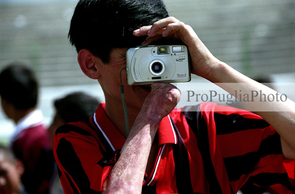 KABUL 24 August 2005..Ghazi Stadium...A disable athlete, wearing the Milan football-club's Tshirt, takes pictures during the Special Olympics games for disables. ..On 23-25 August 2005, Special Olympics Afghanistan held its first national Games at Olympic Stadium in Kabul. More than 300 athletes, including 80 female athletes, experienced a taste of happiness and achievement for the first time in their lives. They competed in athletics, bocce and football (soccer). Because of cultural restrictions, males and females competed at separate venues.