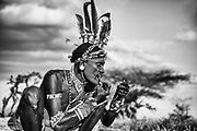 A portrait of a Samburu warrior applying paint to his face, black and white,,Samburu, Kenya, Africa