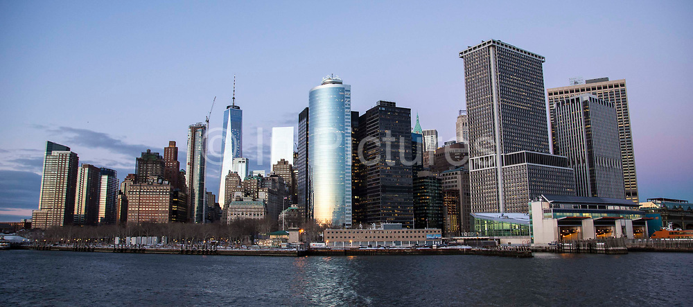 Lower Manhattan, also know as Downtown Manhattan is the financial district and centre for business, culture and government in the city of New York, United States of America.  Photographed in Upper Bay from the Staten Island Ferry at sunset, 27th January 2016.