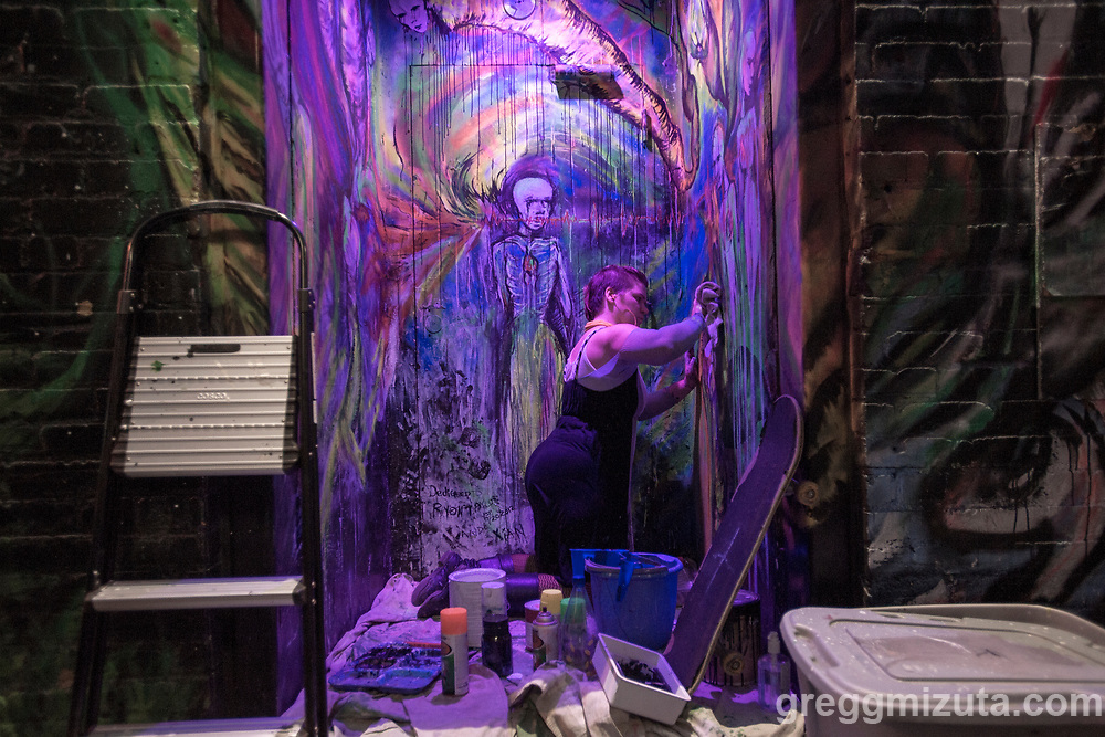 """Candace """"Sprite"""" Rood works on her mural late in the evening of August 5, 2017 during the Freak Alley Gallery seventh annual mural event in downtown Boise, Idaho.<br /> <br /> This is her fourth time she has participated in Freak Alley's mural event. This year she is adding on to the figure she started three years ago. The figures are coming out of the door like a pandora's box. She's been reading the Tibetan Book of the Dead and her mural is referring to the seven gods and their more visceral angry side. They do have a happier side which she would like to incorporate into the mural next year.<br /> <br /> Freak Alley Gallery's week long event provided an """"art-in-motion"""" experience as it welcomed the public to watch artists work on their murals."""