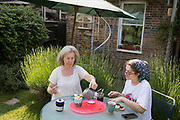 A mother and daughter take tea and scones in the garden at home in south London, on 18th June 2017.