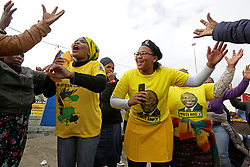 Wednesday 8th May 2019.<br /> Monwabisi Park, Harare,<br /> Khayelitsha, Cape Town, <br /> Western Cape, <br /> South Africa.<br /> <br /> SOUTH AFRICAN GENERAL ELECTIONS 2019!<br /> <br /> SOUTH AFRICAN PROVINCIAL AND NATIONAL ELECTIONS 2019! <br /> <br /> ANC supporters wear ANC colours as they dance and sing political songs together outside the voting station as others stand in a queue nearby waiting to cast their vote at Monwabisi Park, Harare in Khayelitsha near Cape Town, Western Cape, South Africa.<br /> <br /> Registered South African Voters head to the various IEC (Independent Electoral Commission) Voting Stations where they are registered to vote as they cast their votes and take part in voting and other activities on Voting Day 8th May 2019 during the South African General Elections 2019. Voters from across the nation stood in queue's along with many others to vote in the Provincial and National Elections being held in South Africa on Wednesday 8th May 2019.   <br />  <br /> Copyright © Mark Wessels. All Rights Reserved. No Usage Without Permission.<br /> <br /> PICTURE: MARK WESSELS. 08/05/2019.<br /> +27 (0)61 547 2729.<br /> mark@sevenbang.com<br /> studioseven@mweb.co.za<br /> www.markwesselsphoto.com