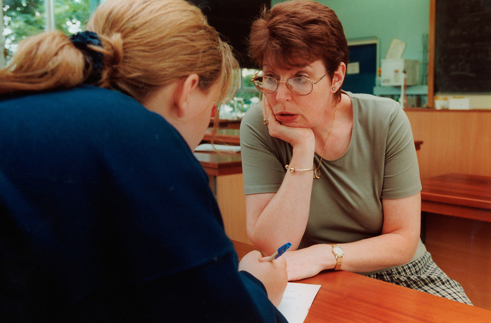 Learning Support Teacher talking with pupil in secondary school classroom; UK