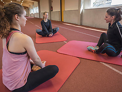 Three women practicing yoga in athletics hall on tartan track, Offenburg, Baden-Wuerttemberg, Germany