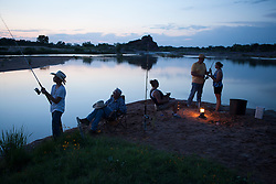 Family fishing together at dusk on the Llano River in Texas.