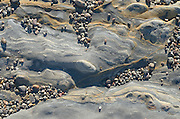 Pebbles shimmer at sunset on a smooth tidal zone rock formation at Weston beach, Point Lobos State Park, California