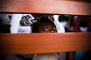 A child looks through the back of a bench at the Osu Maternity Home in Accra, Ghana on Tuesday June 16, 2009.