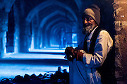 """5th February 2015, New Delhi, India. A man who watches over peoples shoes while they pray sits in the catacombs of Feroz Shah Kotla in New Delhi, India on the 5th February 2015 <br /> <br /> PHOTOGRAPH BY AND COPYRIGHT OF SIMON DE TREY-WHITE a photographer in delhi. + 91 98103 99809. Email:simon@simondetreywhite.com<br /> <br /> People have been coming to Firoz Shah Kotla to leave written notes and offerings for Djinns in the hopes of getting wishes granted since the late 1970's. Jinn, jann or djinn are supernatural creatures in Islamic mythology as well as pre-Islamic Arabian mythology. They are mentioned frequently in the Quran  and other Islamic texts and inhabit an unseen world called Djinnestan. In Islamic theology jinn are said to be creatures with free will, made from smokeless fire by Allah as humans were made of clay, among other things. According to the Quran, jinn have free will, and Iblīs abused this freedom in front of Allah by refusing to bow to Adam when Allah ordered angels and jinn to do so. For disobeying Allah, Iblīs was expelled from Paradise and called """"Shayṭān"""" (Satan).They are usually invisible to humans, but humans do appear clearly to jinn, as they can possess them. Like humans, jinn will also be judged on the Day of Judgment and will be sent to Paradise or Hell according to their deeds. Feroz Shah Tughlaq (r. 1351–88), the Sultan of Delhi, established the fortified city of Ferozabad in 1354, as the new capital of the Delhi Sultanate, and included in it the site of the present Feroz Shah Kotla. Kotla literally means fortress or citadel."""