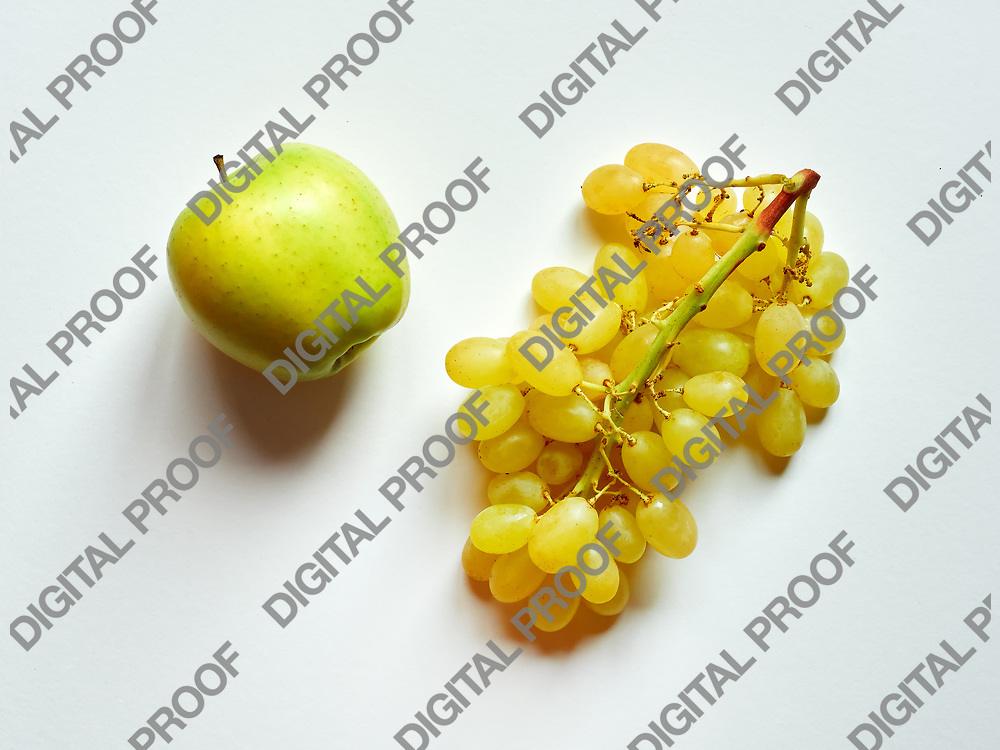 Green apple and bunch of green grapes isolated in studio against a white background viewed from above