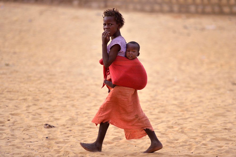 A girl carries her smaller sibling on her back as she walks in Timbuktu, a city in northern Mali which was seized by Islamist fighters in 2012 and then liberated by French and Malian soldiers in early 2013. These children belong to the Bella ethnic group, which has traditionally been exploited by the region's lighter-skinned groups.