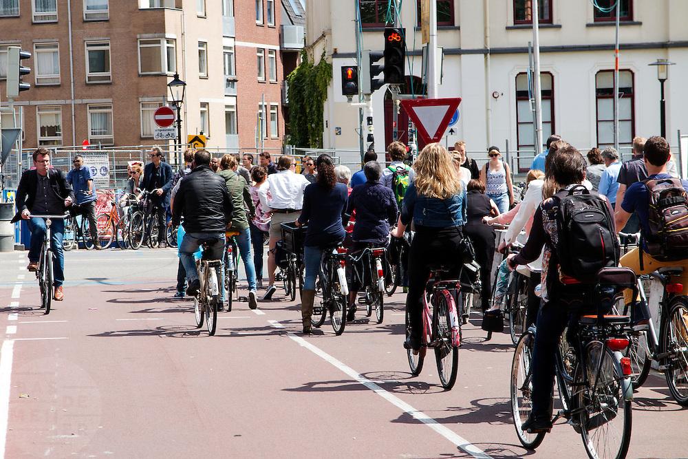 In Utrecht staan fietsers rijen dik te wachten bij het verkeerslicht. Een man rijdt door rood.<br /> <br /> In Utrecht cyclists are waiting at the traffic lights, one man ignores the red light.