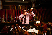 Adrian Weller, the head of Sotheby's Sporting Gun department holds up a double-barelled shotgun alongside a display of beautiful antique firearms and their leather cases. Looking through one barrel with one open eye, he inspects its polished insides used for country sports and rural pursuits. Tagged and chained weapons occupy individual racks in the background. Sotheby's is a multinational corporation, originally English but now owned and headquartered in the United States, that is one of the world's largest auctioneers of fine and decorative art, jewellery, and collectibles. Southeby's auction house have modern and Vintage Sporting Guns, Rifles and shooting accessories dating from 1860 ranging from the earliest breech-loading hammer guns dating from the 1860s to the finest hammerless game guns of the Edwardian era, through to the present day.
