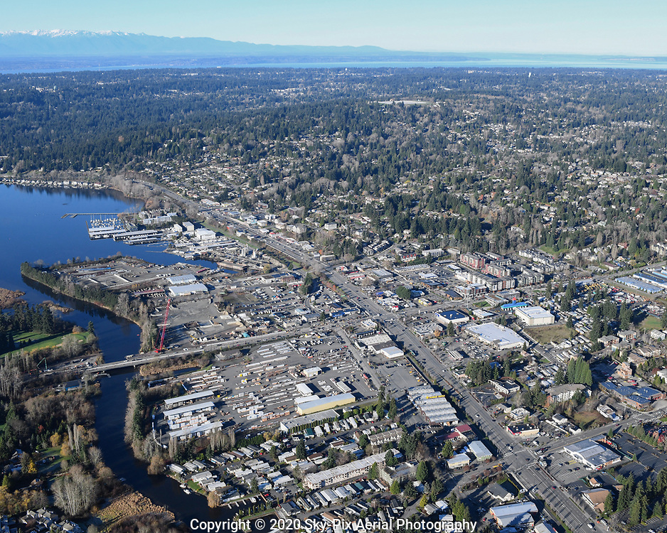 Low oblique territorial aerial view of Kenmore, Washington, at the intersection of 68th Ave NE and Bothell Way NE, looking WNW to Lake Forest Park and Mount Lake Terrace, with North Puget Sound and the Olympic Mountains in the background.
