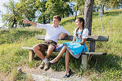 Teenage friends relaxing outdoors on park bench, Bavaria, Germany