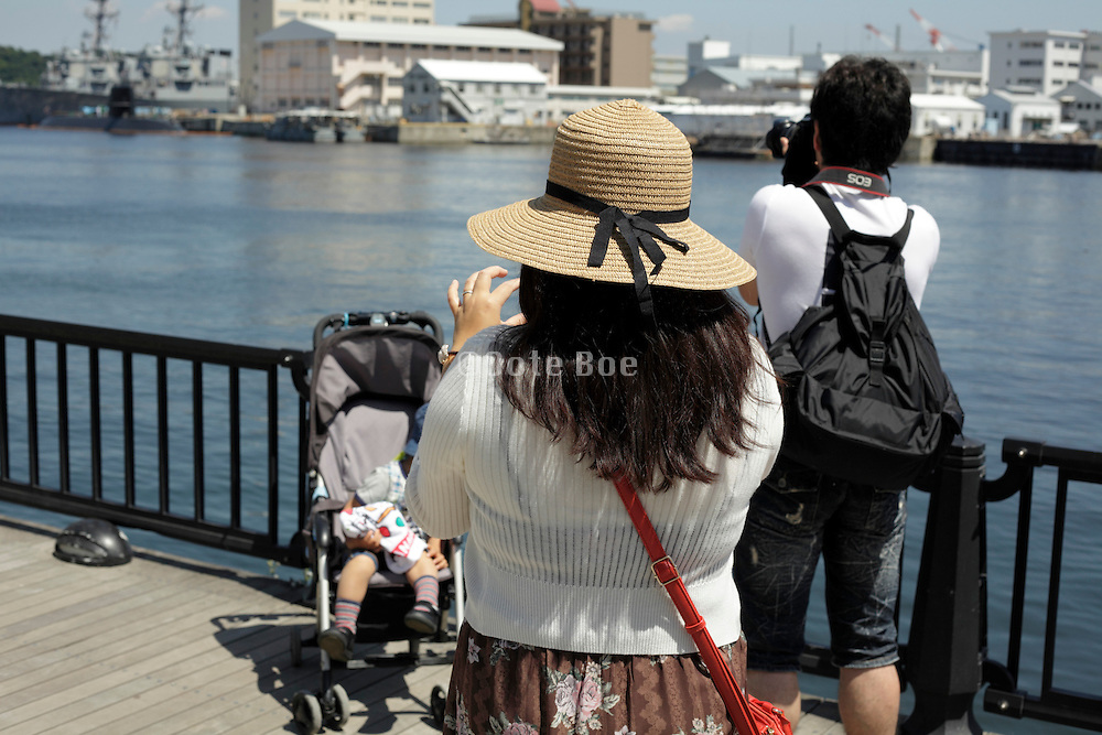 mother taking picture of the child while the husband is making an image of the waterscape