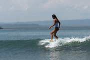 An attractive female Indonesian longboarder surfing at Batu Karas beach on the 31st October 2019 in Java in Indonesia.