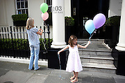 A young girl and her mother prepare for the child's birthday party by tying balloons to the railings of their fine house in this exclusive and classically-designed location in Belgravia, London. The pastel-coloured balloons are helium-filled and rise up in a breeze as the girl smiles to herself. 103 Eaton Place faces Eaton Square, one of London's three garden squares built by Thomas Cubitt and the Grosvenor family when they developed the main part of Belgravia from 1826 until 1855. Belgravia attracts actors, politicians, ambassadors, big-budget bankers, traders and Prime Ministers like Neville Chamberlain and Stanley Baldwin at number 93.