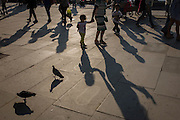Pigeons and family with children walk along London's Southbank.