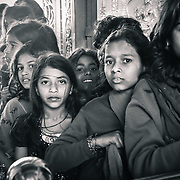Multiple face expressions among these teenage indian girls queuing up to enter a temple.