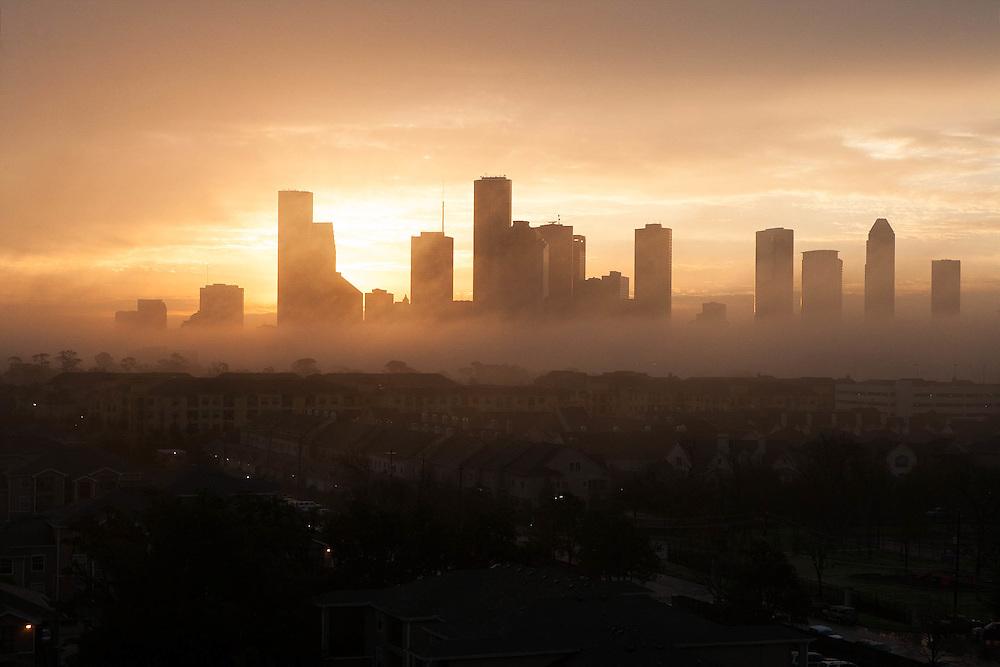Sun setting behind the silhouetted Houston, Texas skyline.