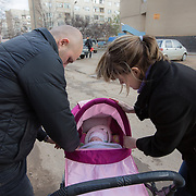 CAPTION: Parents Nina and Aleksander know that their daughter Valentina must be in good health for her cleft lip surgery tomorrow, so they take care to ensure she is cosy and warm as they brave the winter air. LOCATION: Volzhskiy, Volgograd Oblast, Russia. INDIVIDUAL(S) PHOTOGRAPHED: Aleksander Panteleeyev (father), Nina Panteleeyeva (mother) and Valentina Panteleeyeva (baby).