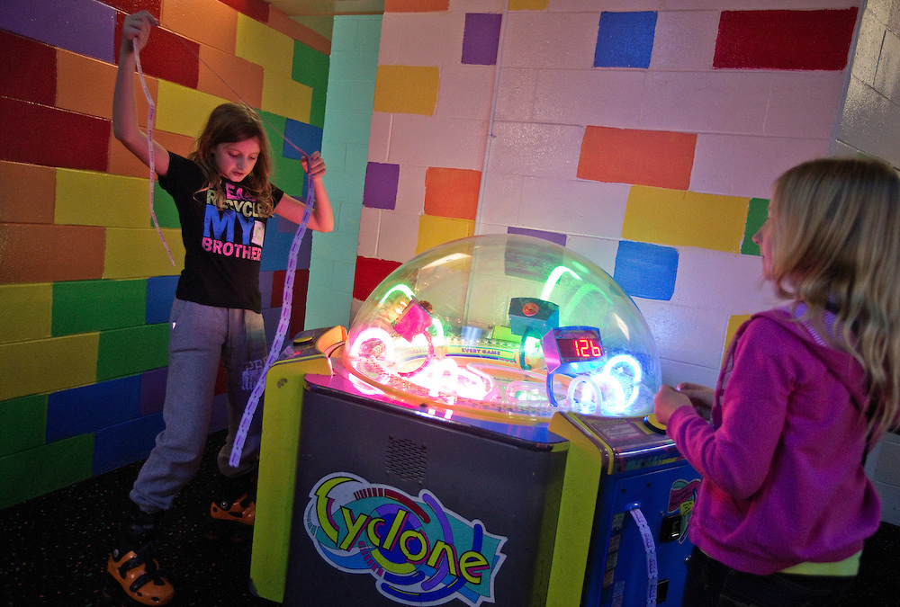 Melanie Mackey, 10, collects a large string of tickets while playing a game with Carlita John, 10, during Skate Island's 48th annual New Year's Eve party Tuesday night in Grand Island. (Independent/Matt Dixon)