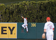 The Angels' Mike Trout climbs the center field wall to rob the Mariners' Jesús Montero of a three-run home run in the top of the fourth inning Saturday night at Angel Stadium.
