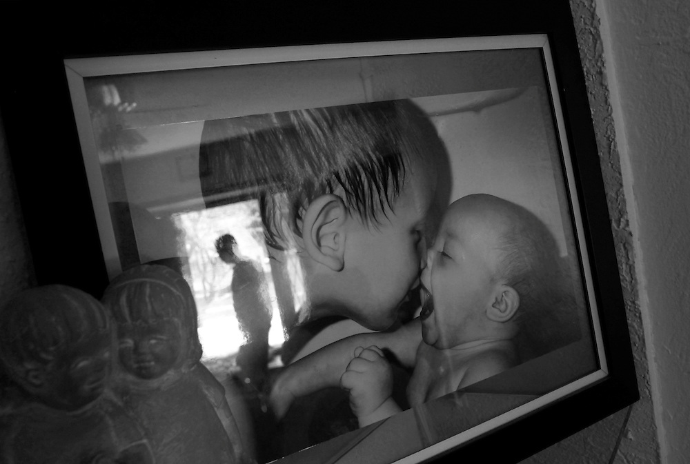 Parker Roos, who suffers from Fragile X, is reflected in a photograph of when he was a young boy with his sister at his home in Canton, Illinois, April 4, 2012.  REUTERS/Jim Young
