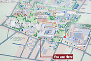 An arrow pointing to the You Are Here location on a map of Bradford's University, showing the campus streets, roads, buildings and landmarks of this Yorkshire college.