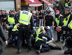 © Licensed to London News Pictures. 13/10/2018. London, UK. A supporter of The Democratic Football Lads Alliance is tackled to ground with police after clashing with a counter demonstration organised by Stand Up To Racism and Unite Against Fascism. The FLA were due to hold a silent march in Central London. Strict conditions have been imposed upon the march to prevent 'serious disorder' following previous demonstrations.  Photo credit : Tom Nicholson/LNP