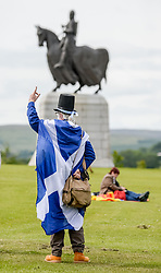 Pictured: Marcher readies his banner with King Robert the Bruce monument in the background.<br /> <br /> An estimated 7000 people marched through Bannockburn near Stirling in support of Scottish independence, in the latest march organised by the 'All Under One Banner' group.<br /> <br /> © Dave Johnston / EEm