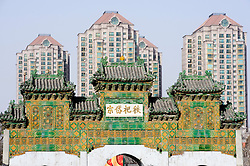 Contrast between historic monument and modern highrise apartment buildings in central Beijing China