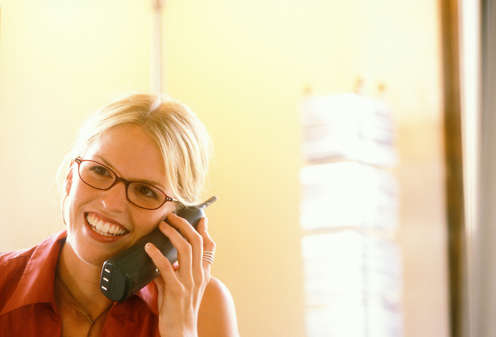 A young businesswoman smiling while talking on the telephone.