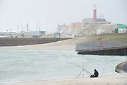 The Hague, South-Holland/Netherlands - 200222: Sea fishing fisherman on a beach near the harbour of Scheveningen.